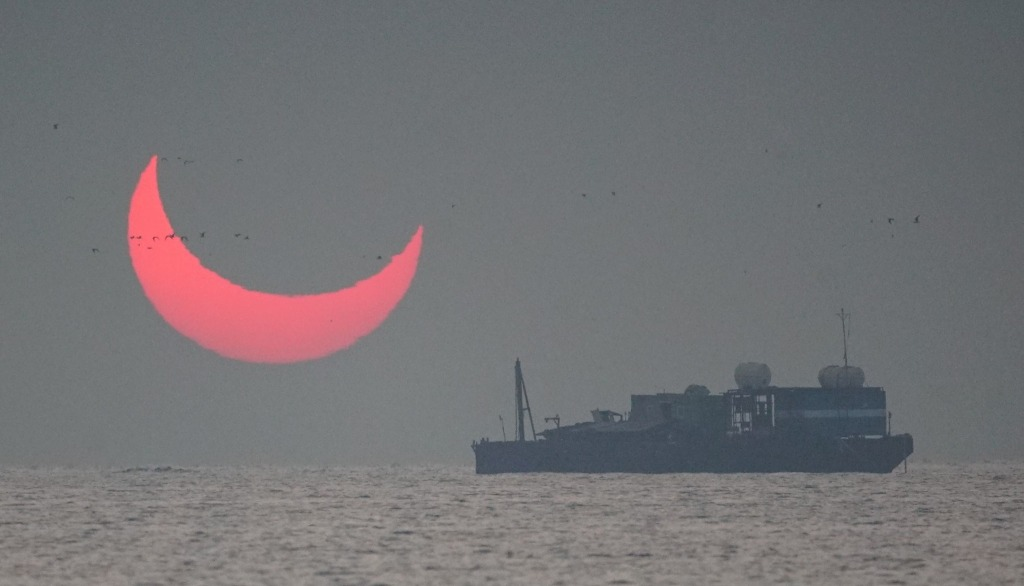 "The sun, partially blocked by the moon, rises above the sea in Al Wakrah, Qatar, Dec. 26, 2019. Facebook and Twitter users were quick to draw comparisons between the reddened partial eclipse to ""devil horns."""