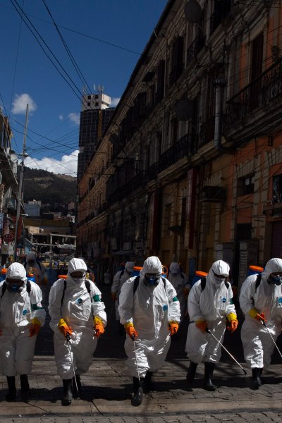 City workers fumigate a street to help contain the spread of the new coronavirus in La Paz, Bolivia, Thursday, April 2, 2020.