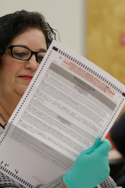 In this May 30, 2018, file photo, Beverly Darm, an election clerk at the Sacramento County Registrar of Voters, inspects a mail-in ballot in Sacramento, Calif.