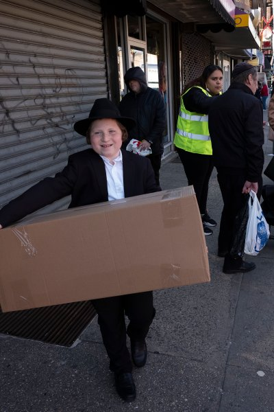 A boy carries a box of matzos for Passover that he picked up from his synagogue in the Brooklyn borough of New York.