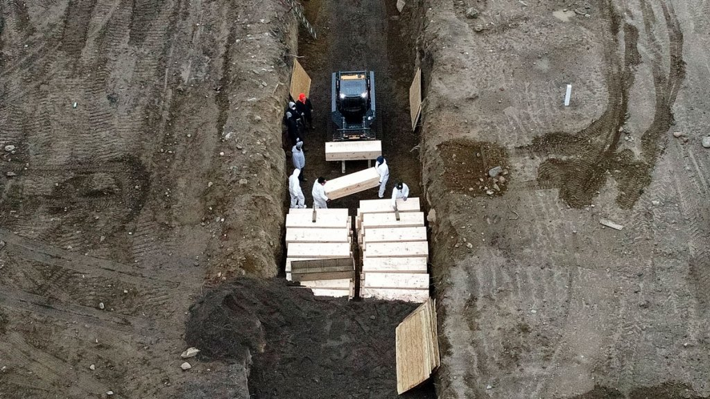 Workers wearing personal protective equipment bury bodies in a trench on Hart Island, Thursday, April 9, 2020, in the Bronx