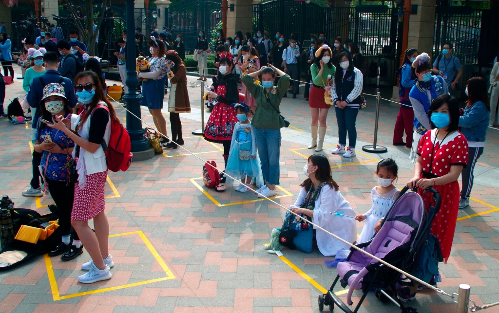 Visitors, wearing face masks, wait to enter the Disneyland theme park in Shanghai as it reopened, Monday, May 11, 2020.