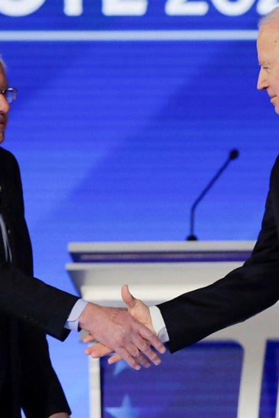 FILE - Democratic presidential candidates Sen. Bernie Sanders, I-Vt., left, and former Vice President Joe Biden shake hands on stage, Feb. 7, 2020, before the start of a Democratic presidential primary debate in Manchester, N.H.