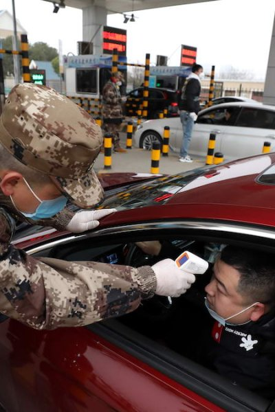 A militia member checks the body temperature of a driver on a vehicle at an expressway toll gate in Wuhan in central China's Hubei province, Jan. 23, 2020, in a bid to contain the spread of the new coronavirus.