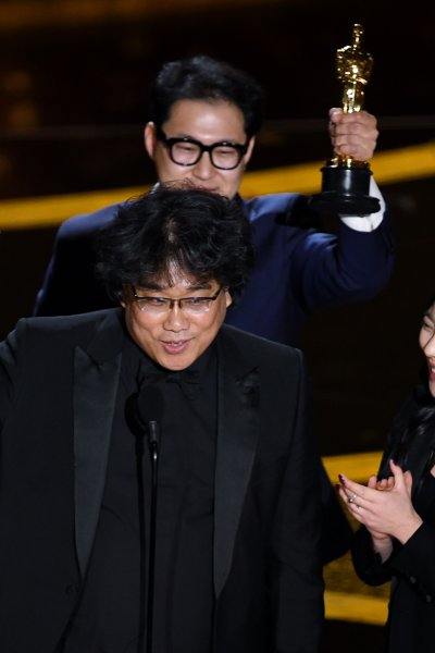 Bong Joon-ho and Han Jin-won accept the Writing - Original Screenplay - award for 'Parasite' with interpreter Sharon Choi onstage during the 92nd Annual Academy Awards at Dolby Theatre on February 09, 2020 in Hollywood, California.