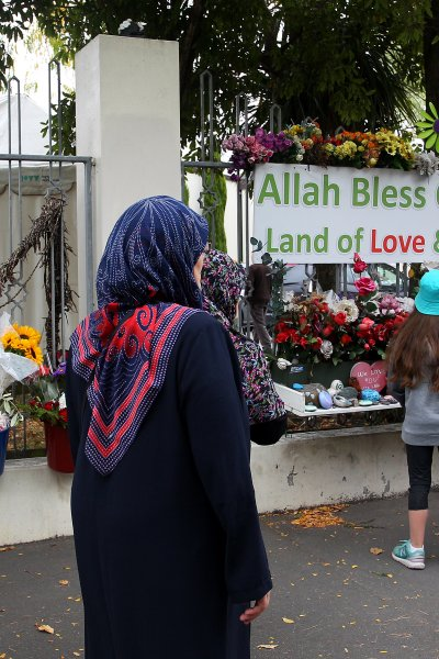 A family lays flowers at the entrance of the Masjid An-Nur mosque