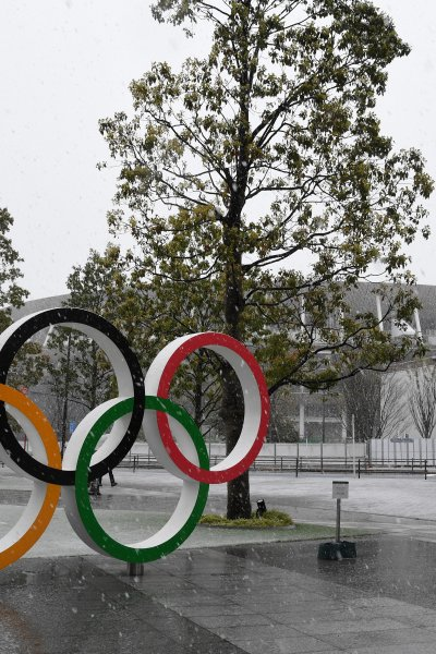 The Olympic rings are displayed in front of the National Stadium while snow falls