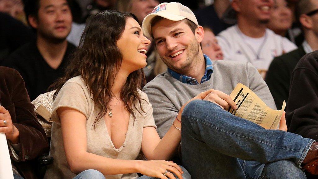 Ashton Kutcher and Mila Kunis smile during basketball game