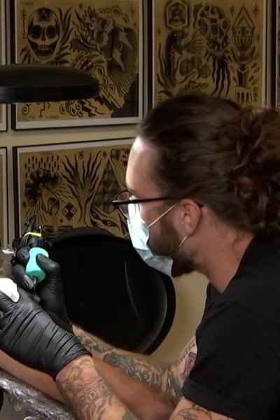 A tattoo artist works on covering a racist image on a customer's arm (for NBCLX)