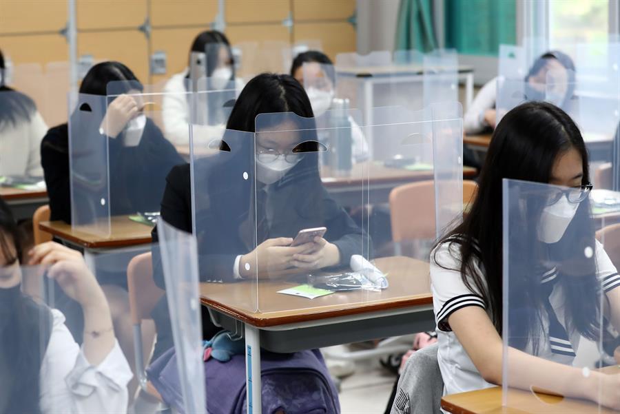 Los estudiantes esperan que la clase comience con paneles de plástico colocados en sus escritorios en la Escuela Secundaria Jeonmin en Daejeon, Corea del Sur.