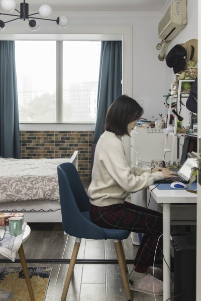 In this file photo, Claire Tu, an employee at Reprise Digital, works from her home in Shanghai, China, on Monday, March 9, 2020.