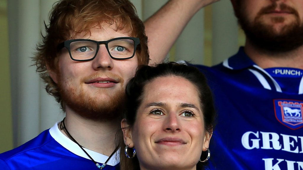 In this April 21, 2018, file photo, musician Ed Sheeran and Cherry Seaborn look on during the Sky Bet Championship match between Ipswich Town and Aston Villa at Portman Road in Ipswich, England.