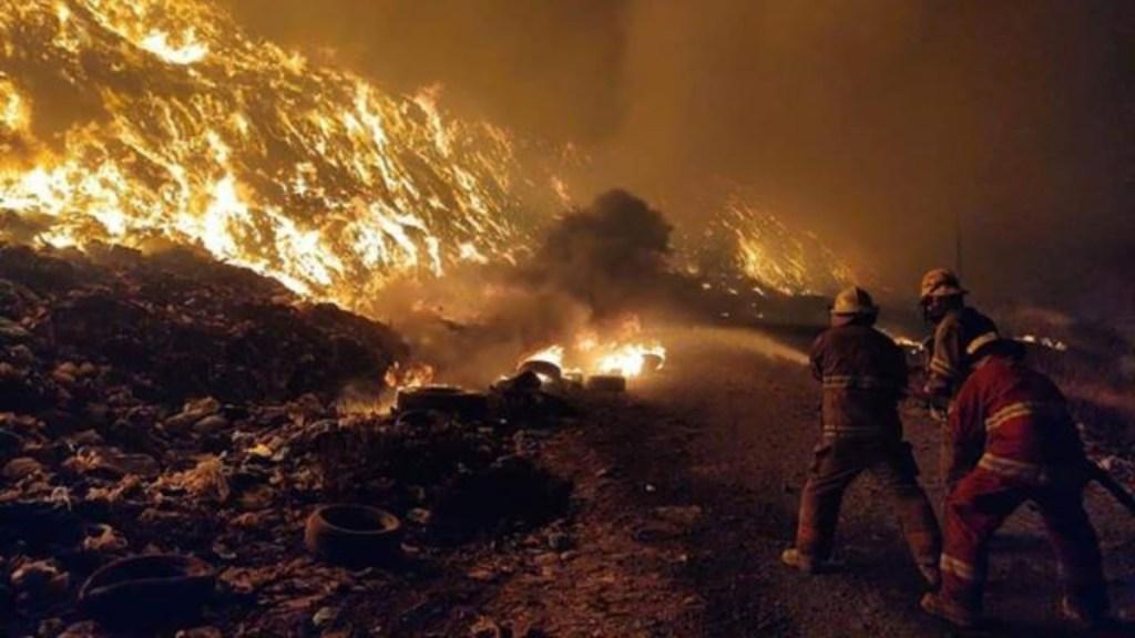 Bomberos de Uruapan, coordinados por el primer comandante Raúl Ortiz Padilla, trabajan para sofocar el incendio en el tiradero municipal.
