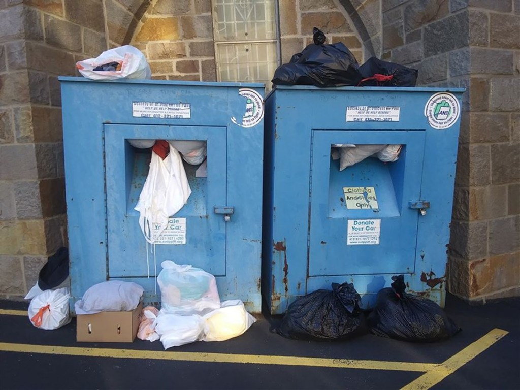 Donation drop off boxes with bags overflowing