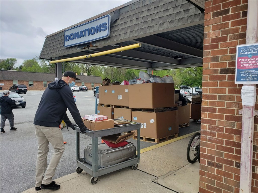 Man pushing a cart of donations