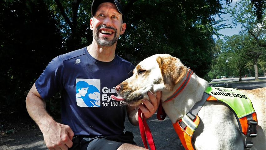 Thomas Panek pauses with his Labrador retriever, Blaze, a trained guide dog, after running in Central Park, July 23, 2020, in New York. Panek, an accomplished runner who is blind, developed a canine running guide training program.
