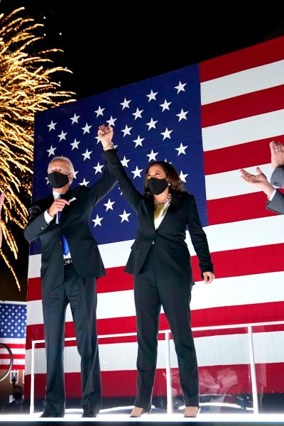 Democratic presidential candidate former Vice President Joe Biden, with Democratic vice presidential candidate Sen. Kamala Harris, D-Calif., raise their arms up as fireworks go off in the background during the fourth day of the Democratic National Convention, Thursday, Aug. 20, 2020, at the Chase Center in Wilmington, Del. Looking on are Jill Biden, far left, and Harris' husband Doug Emhoff, far right.