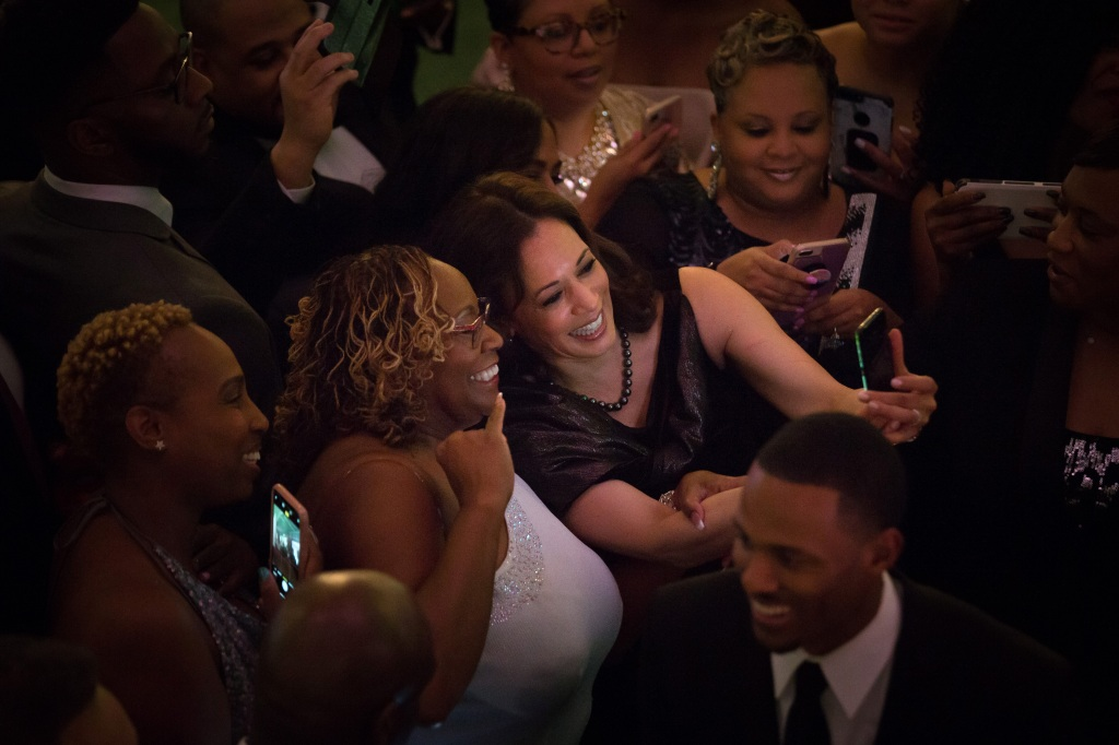 Senator Kamala Harris, a Democrat from California, uses a mobile device to take a selfie photograph with an attendee during the Alpha Kappa Alpha Sorority Inc. Annual Pink Ice Gala in Columbia, South Carolina, U.S., on Friday, Jan. 25, 2019.