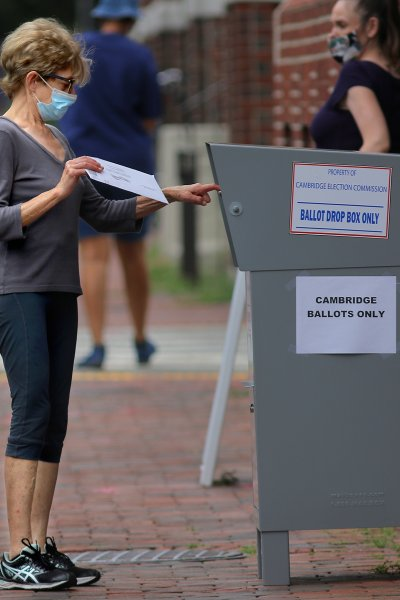 A voter drops off a mail-in ballot in a collection box outside the Cambridge City Hall Annex at the corner of Broadway and Inman Street in Cambridge, MA on Aug. 25, 2020.