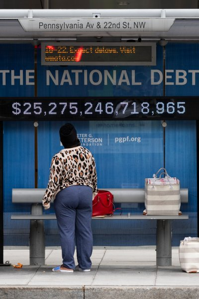 Passengers wearing face masks wait for their bus in front of a national debt display on Pennsylvania Ave. NW in Washington.