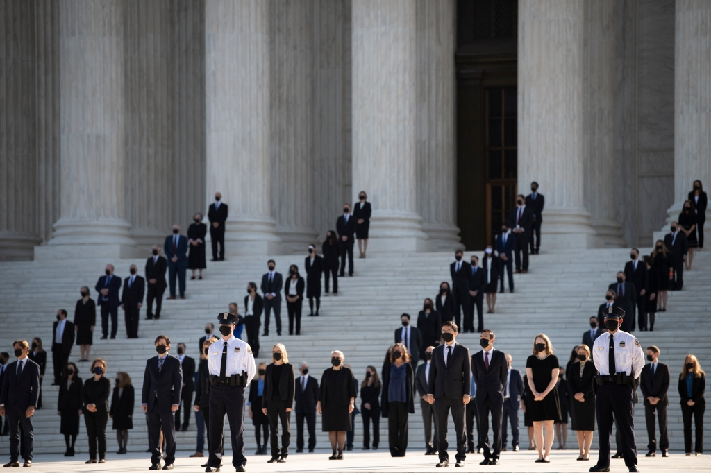 Former law clerks walk out and stand as Justice Ruth Bader Ginsburg's casket arrives at the Supreme Court in Washington, Sept. 23, 2020.