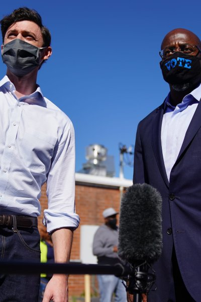 In this Oct. 3, 2020, file photo, Democratic U.S. Senate candidates Jon Ossoff and Rev. Raphael Warnock hand out lawn signs at a campaign event in Lithonia, Georgia.