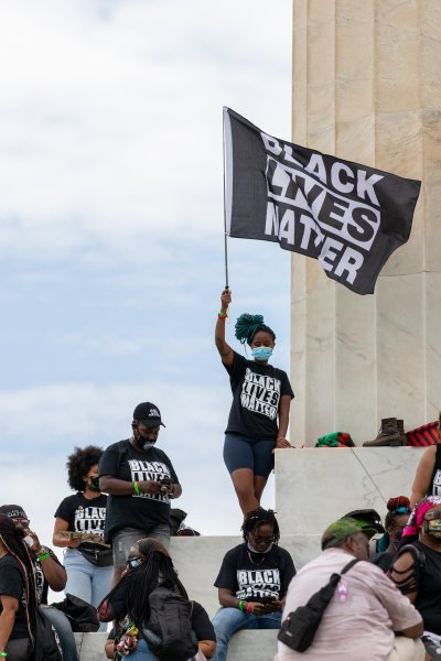 """In this Aug. 28, 2020, file photo, a demonstrator wearing a protective mask waves a """"Black Lives Matter"""" flag on the steps of the Lincoln Memorial during the """"Get Your Knee Off Our Necks"""" march on Washington in Washington, D.C."""