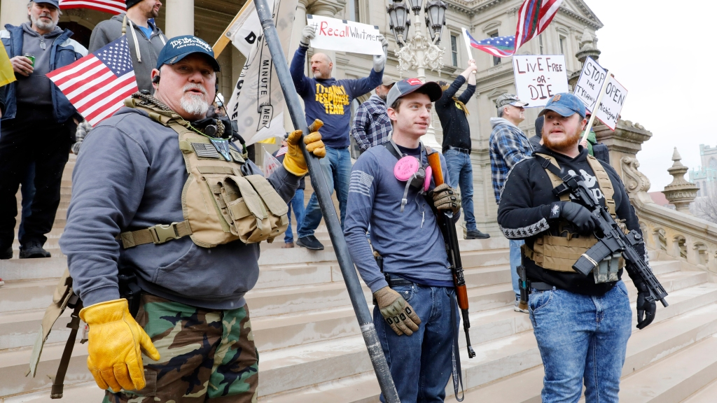 "People take part in a protest for ""Michiganders Against Excessive Quarantine"" at the Michigan State Capitol in Lansing, Michigan on April 15, 2020."