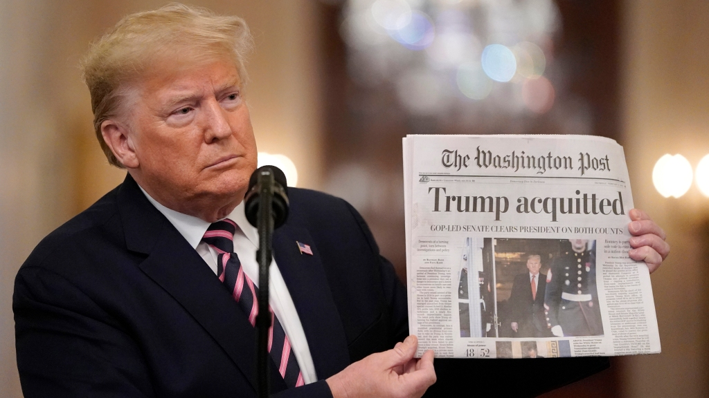 President Donald Trump holds a copy of the Washington Post as he speaks in the East Room of the White House the day after he was acquitted on two articles of impeachment by the Senate, Feb. 6, 2020, in Washington, D.C.