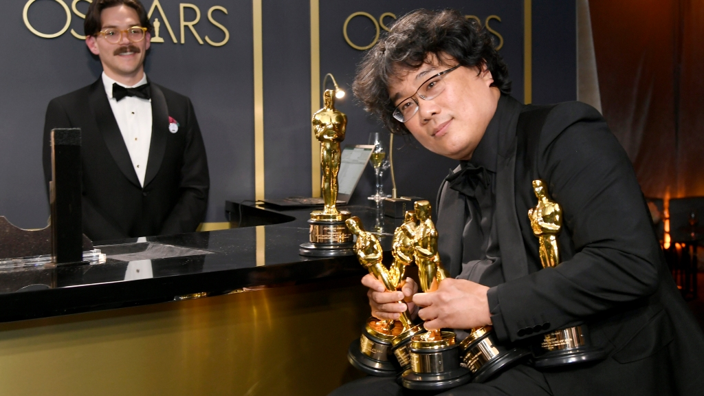 "Writer-director Bong Joon-ho, winner of the Best Picture, Director, Original Screenplay, and International Feature Film awards for ""Parasite,""  holds the trophies won by his black comedy flick at the 92nd Academy Awards Governors Ball at Hollywood and Highland on Feb. 9, 2020, in Hollywood, California."