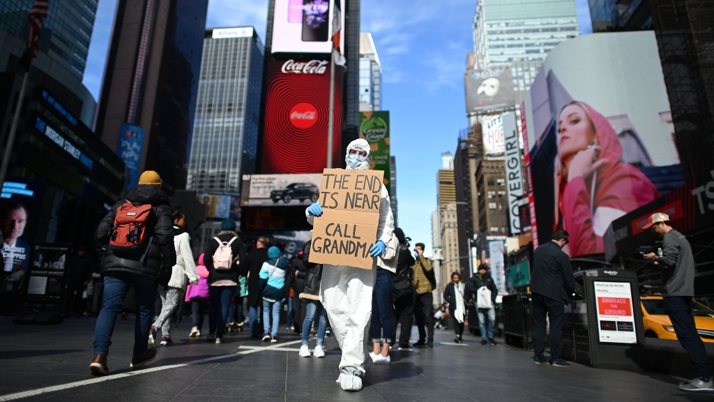 A man wearing a hazmat suit and a mask walks down an emptied Times Square on March 14, 2020 in New York City.