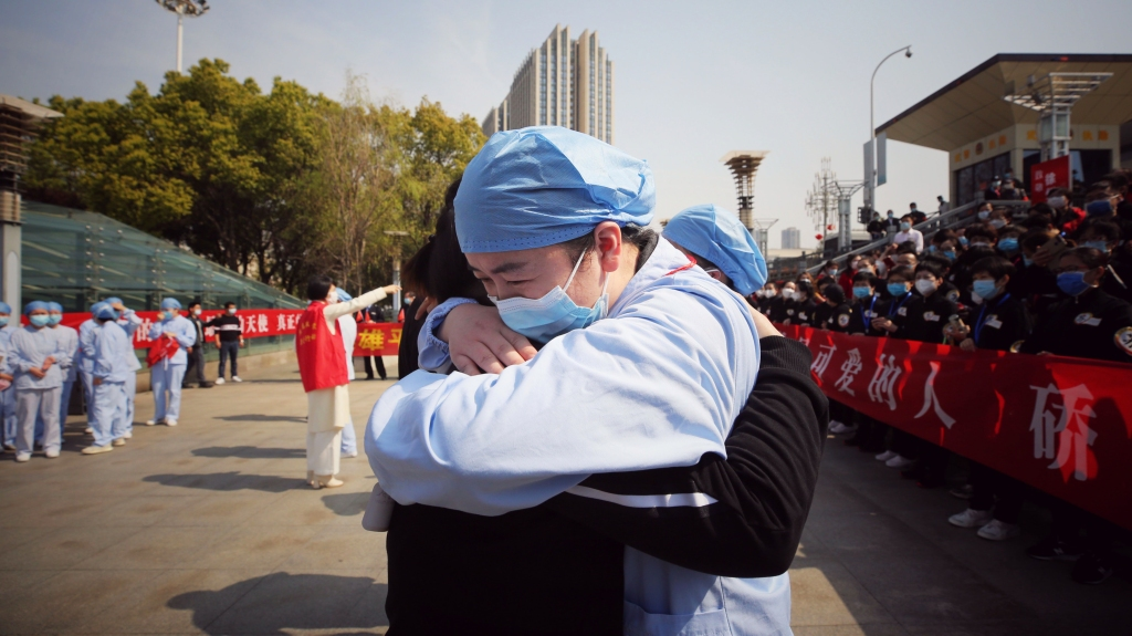 A medical worker, right, hugs a member of a medical assistance team from Jiangsu at a ceremony marking their departure after helping with the COVID-19 coronavirus recovery effort, in Wuhan, China, March 19, 2020.