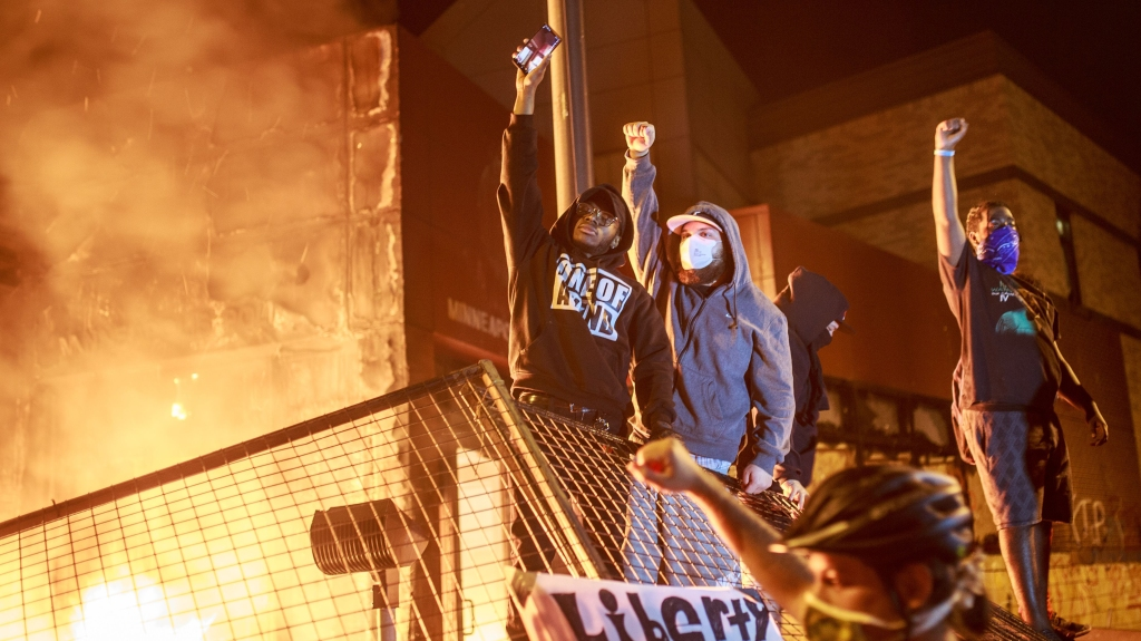 Protesters raise their fists as flames rise behind them in front of the Third Police Precinct on May 28, 2020, in Minneapolis, Minnesota, during a protest over the death of George Floyd.