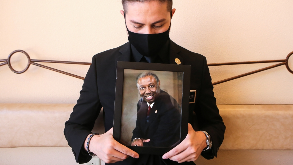 Jorge Ortiz, general manager of Perches Funeral Homes, displays a photo of deceased colleague Bishop Harrison Johnson on Nov. 14, 2020 in El Paso, Texas. Texas eclipsed one million COVID-19 cases on November 11th, with El Paso holding the most cases statewide.