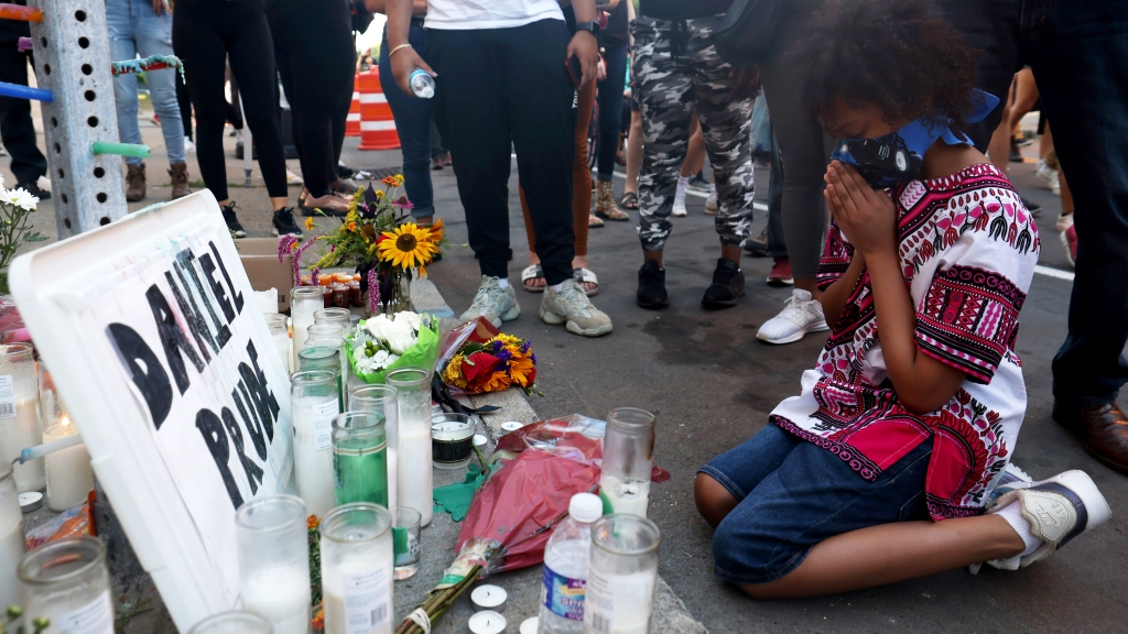 "Hasan Massey Jr., 11, kneels in prayer at a make-shift memorial at the site where Daniel Prude was arrested on Sept. 3, 2020, in Rochester, New York. Prude died after being arrested by Rochester police officers who had placed a ""spit hood"" over his head and pinned him to the ground while restraining him."