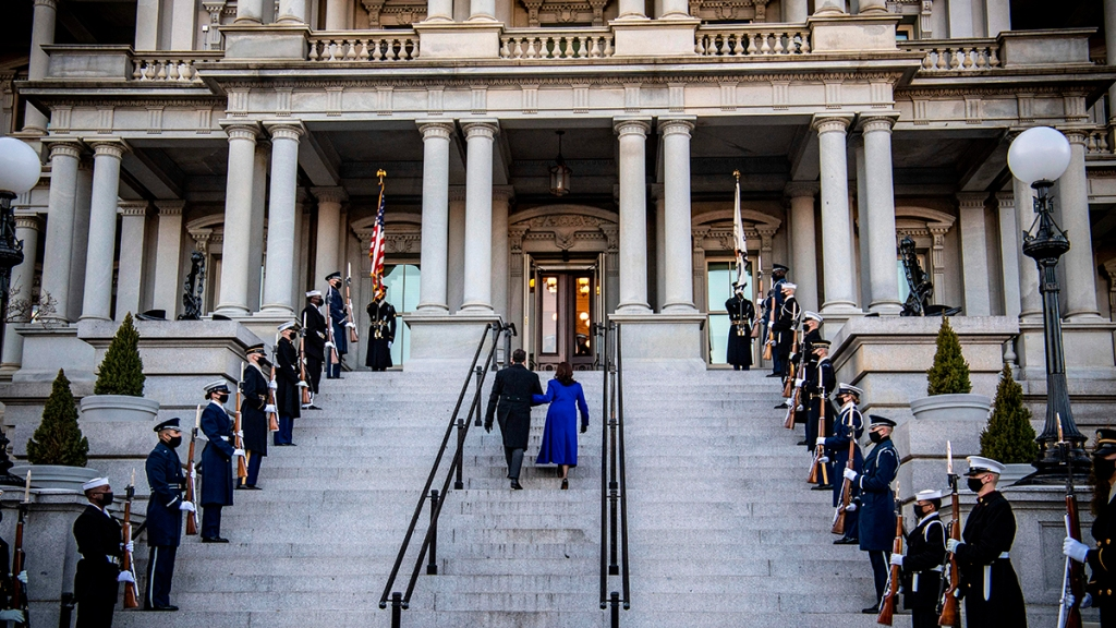 Vice President Kamala Harris (C) and US Second Gentleman Doug Emhoff walk up the stairs of the Eisenhower Building