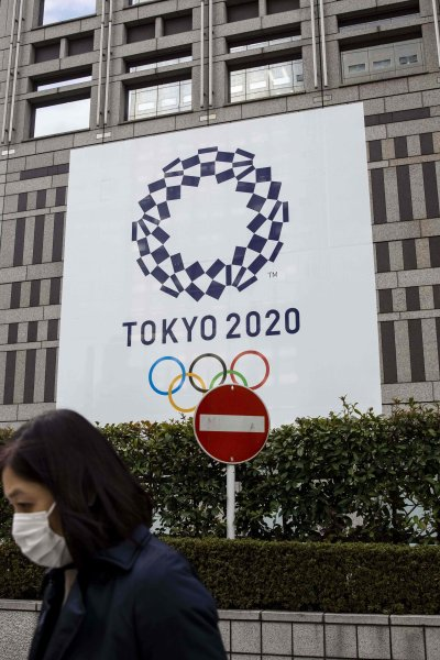In this Jan. 22, 2021, file photo, a pedestrian walks past a traffic sign next to an official Tokyo 2020 Olympic Games banner hanging on the Tokyo Metropolitan Government Building.