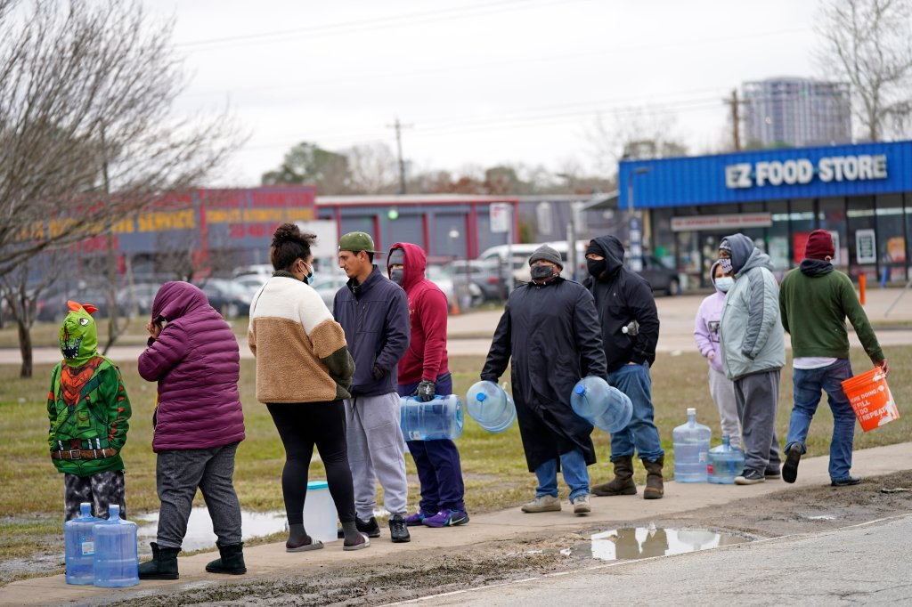 People wait in near freezing temperatures to fill containers with water from a park spigot Thursday, Feb. 18, 2021, in Houston. Houston and several surrounding cities are under a boil water notice as many residents are still without running water in their homes.