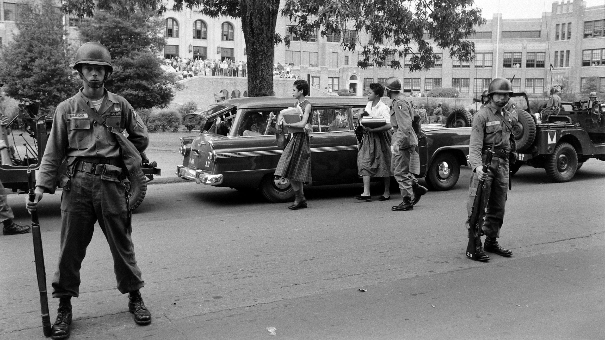 The Arkansas National Guard escorts Carlotta Walls LaNier and a fellow member of the Little Rock Nine on the grounds of Little Rock Central High School, September 1957.