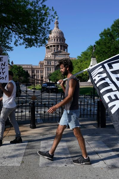 Two people stand outside of the Texas Capitol with a sign and a Black Lives Matter flag after the guilty verdict in the George Floyd trial.