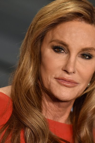 Caitlyn Jenner looks into camera wearing red dress.