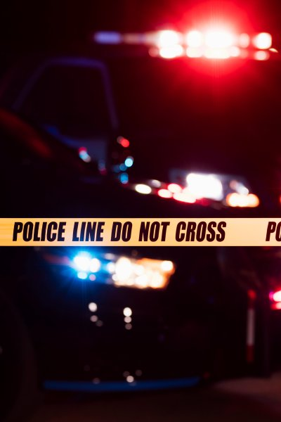 Police sirens flash behind a strip of crime scene tape.