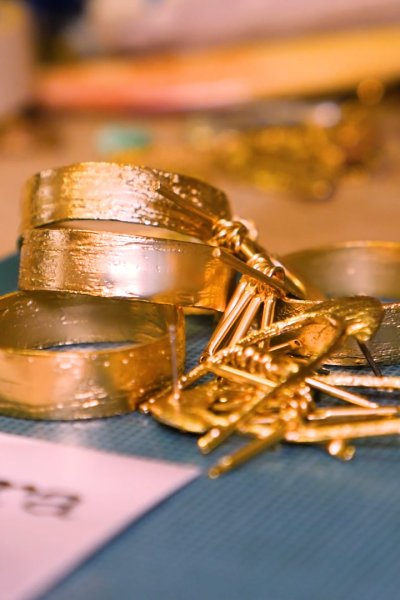 Close-up of gold jewelry on a worktable.
