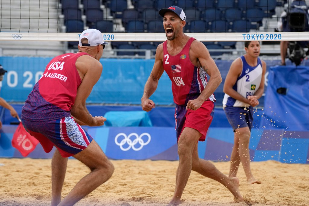 Nicholas Lucena, center, of the United States, celebrates with teammate Philip Dalhausser as Alvaro Morais Filho, right, of Brazil, watches during a men's beach volleyball match at the 2020 Summer Olympics, Tuesday, July 27, 2021, in Tokyo, Japan.