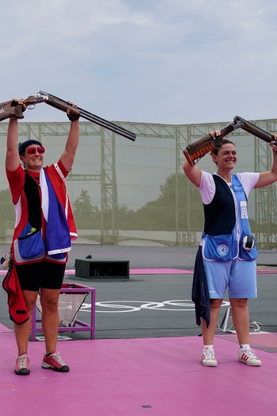 Women's trap shooting medalists hold up their guns