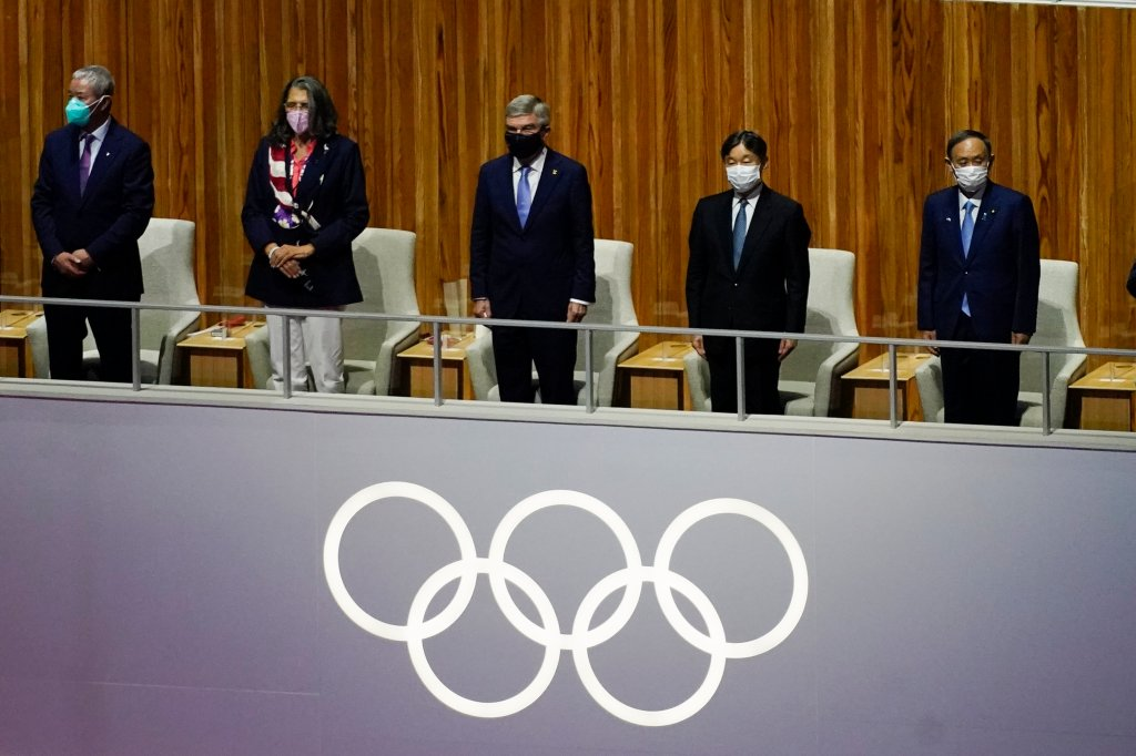 The President of the International Olympic Committee Thomas Bach and others stand during a moment of silence for victims of COVID-19 during the opening ceremony at the Olympic Stadium at the 2020 Summer Olympics, Friday, July 23, 2021, in Tokyo.
