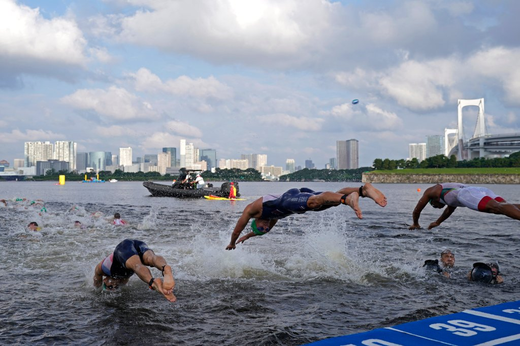 Morgan Pearson of the United States, center, dives into the water for the start of the men's individual triathlon at the 2020 Summer Olympics on July 26, 2021, in Tokyo, Japan.