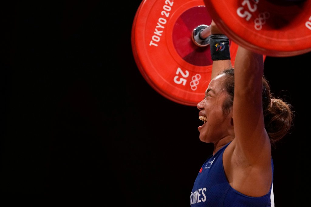 Hidilyn Diaz of Philippines celebrates as she competes and sets new world record and won the gold medal in the women's 55kg weightlifting event, at the 2020 Summer Olympics on July 26, 2021, in Tokyo, Japan.