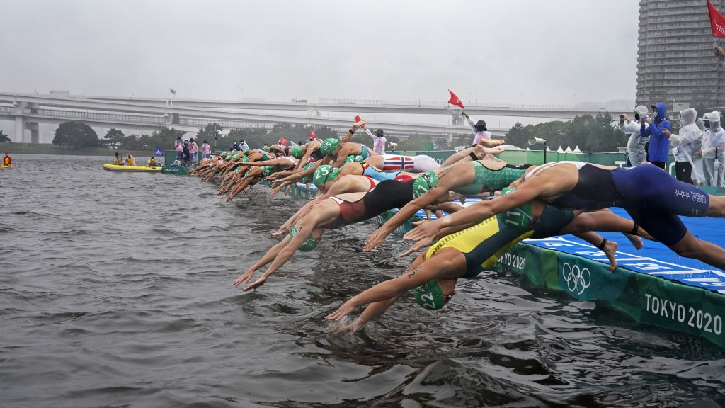 Taylor Knibb of The United States (11) and Emma Jeffcoat of Australia (22) dive into the water for the start of the women's individual triathlon competition at the 2020 Summer Olympics, Tuesday, July 27, 2021, in Tokyo, Japan.