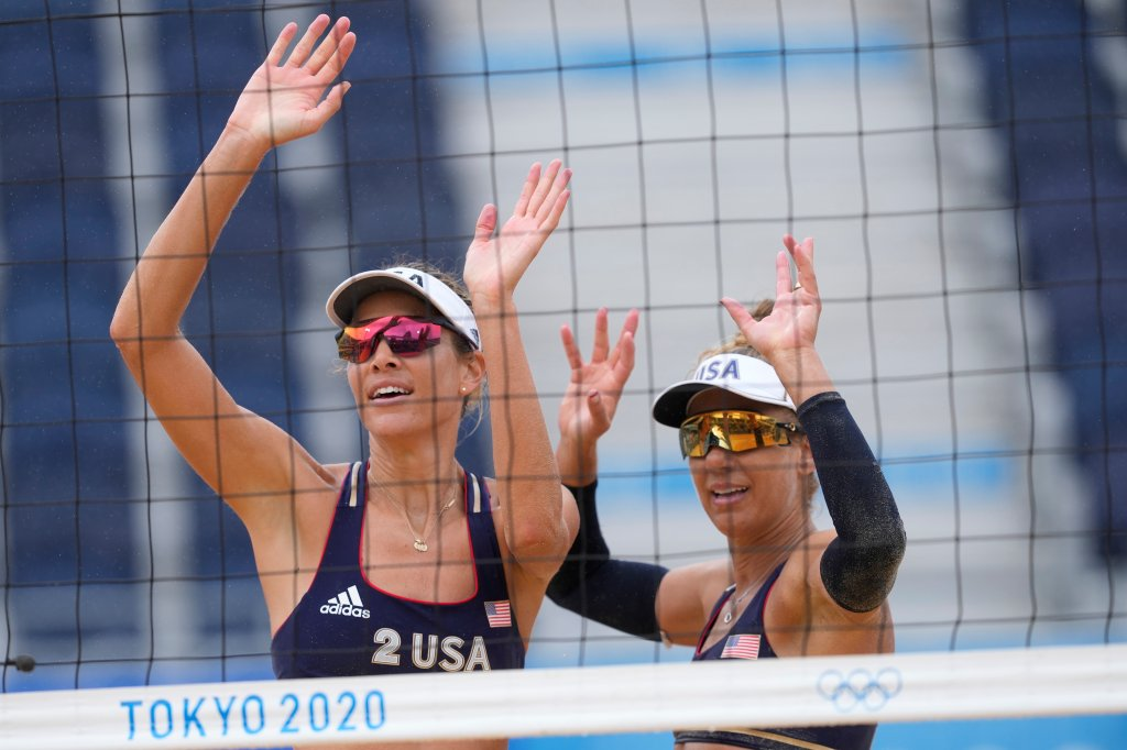 April Ross, right of the United States, and teammate Alix Klimeman wave after winning a women's beach volleyball match against Spain at the 2020 Olympics on July 27, 2021, in Tokyo, Japan.